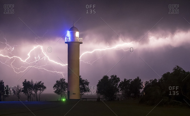 Modern lighthouse in a lightning storm at night