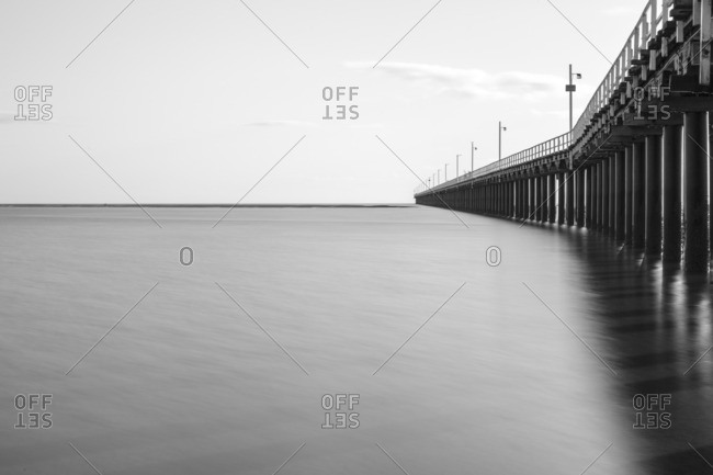 Calm ocean water beneath a wooden pier