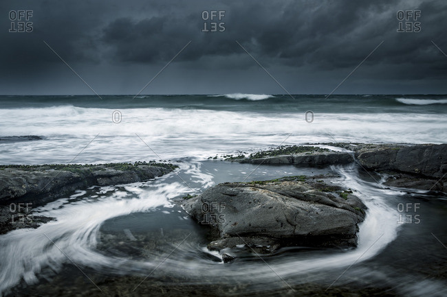 Tide swirling around rocks on a seashore in a storm