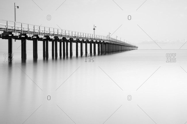 Ocean pier over calm misty water