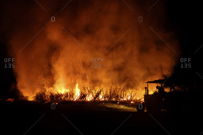 Man on a tractor beside a wildfire burning at night