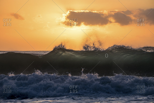Waves crashing on a seashore at sunrise