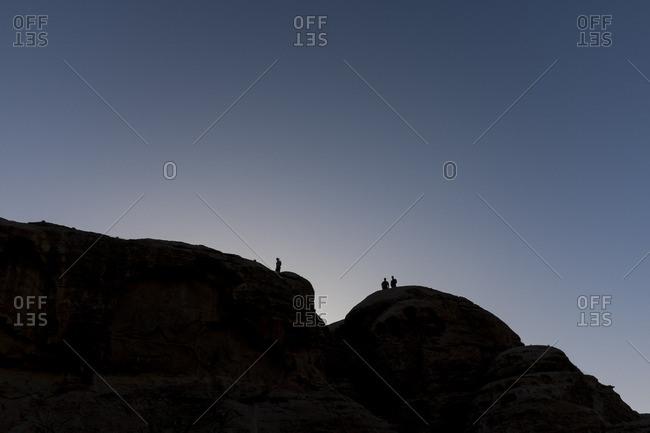 Silhouettes of people walking on top of desert cliffs at sunset