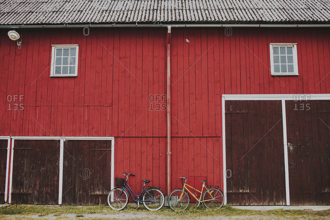 September 20, 2014: September 20, 2014: Two bicycles leaning on a the side of a red barn