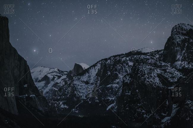 Starry sky over wintery mountain landscape