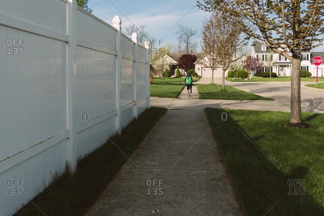 Boy scooting down sidewalk in a residential neighborhood from behind