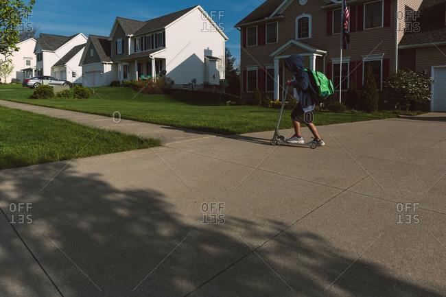 Boy riding scooter down sidewalk in a residential neighborhood