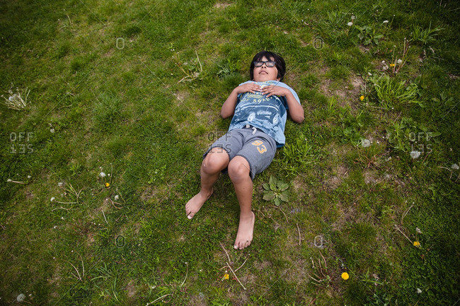 Boy lying in the grass sleeping