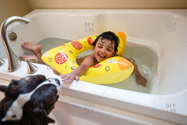Boy taking bath with inflatable floatie