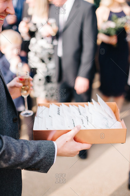 Person handing out envelopes for guests at wedding reception