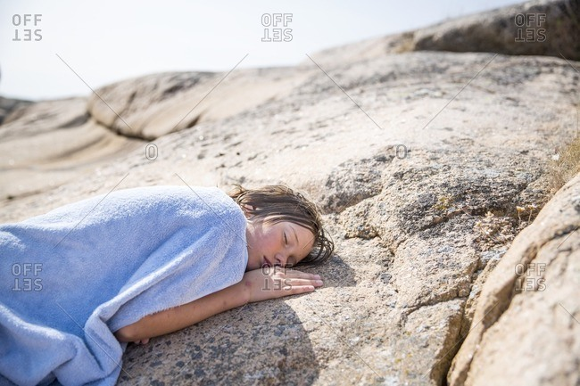 Boy covered with blanket sleeping on rock