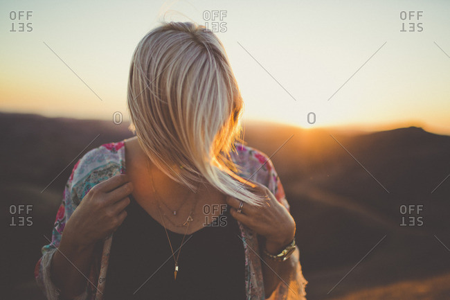 Blonde woman in mountain sunlight