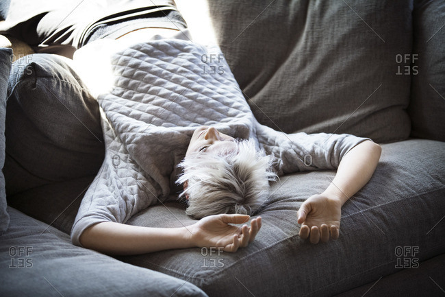 Young woman lying upside down on sofa at home