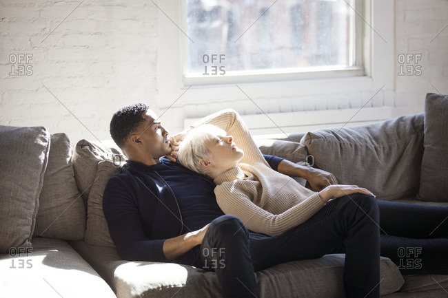 Multi-ethnic couple relaxing on sofa at home