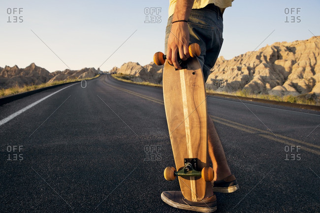 Low section of man holding skateboard while standing on country road on desert