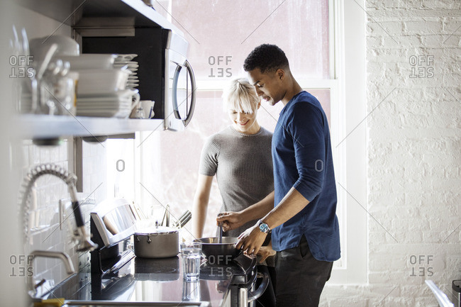 Multi-ethnic couple preparing food in kitchen