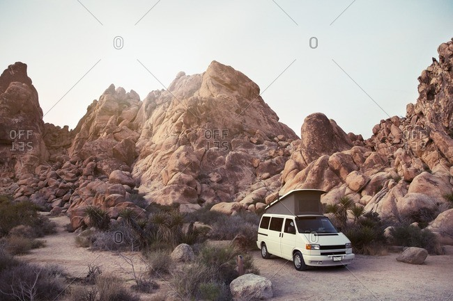Joshua Tree, CA, USA - February 28, 2016: Van parked by mountains against clear blue sky