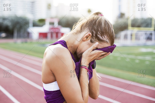 Side view of female athlete wiping sweat on face with tank top
