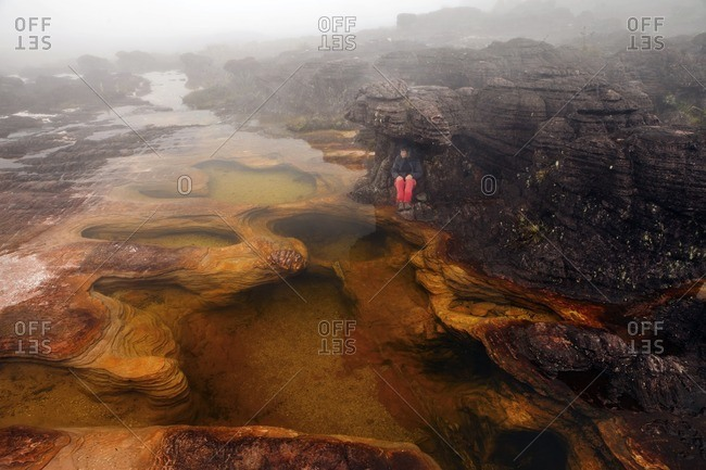 High angle view of woman sitting on rock by lake in foggy weather