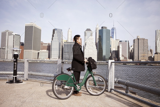 Side view of businessman with rental bike enjoying city view from observation point
