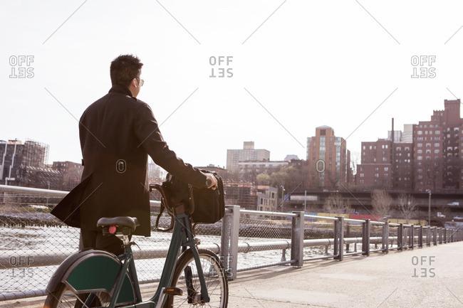 Rear view of businessman walking with rental bike on footpath in city
