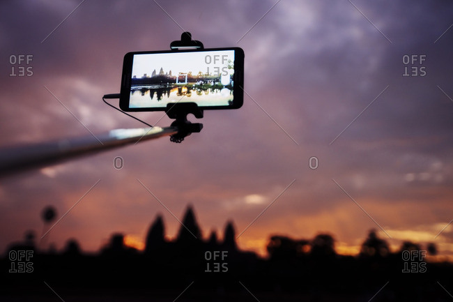 Low angle view of smart phone attached to monopod photographing silhouette Angkor Wat temple during sunset