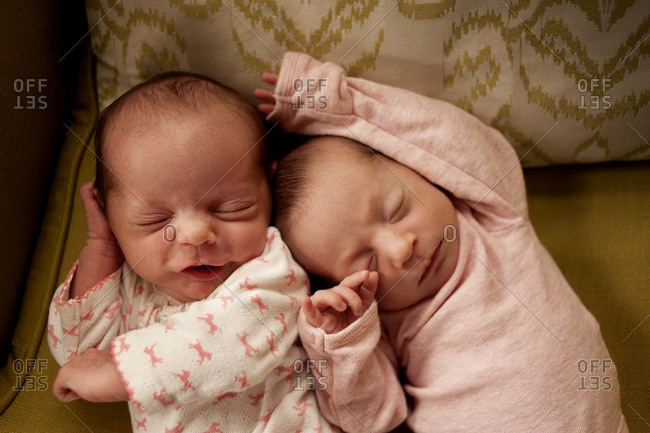 Overhead view of baby girls relaxing on sofa