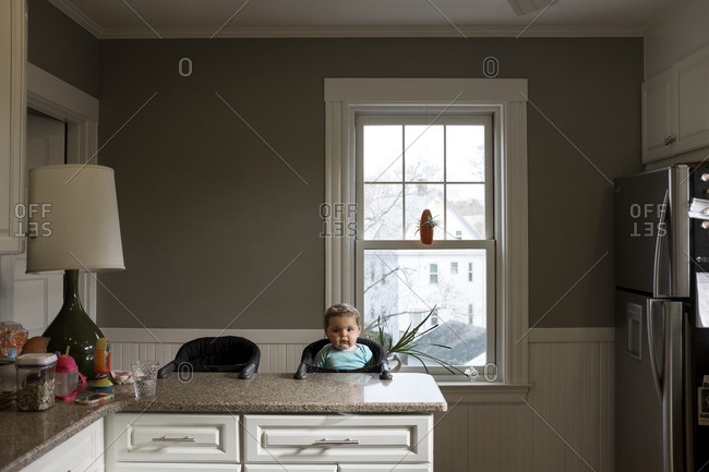 Cute baby girl sitting high chair in kitchen