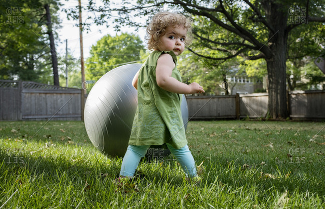 Rear view portrait of cute girl standing with fitness ball at lawn