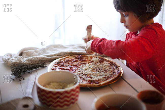 Boy preparing pizza at home