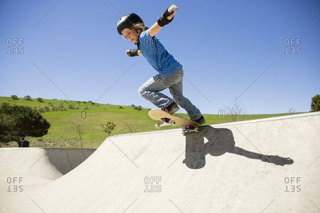 Low angle view of boy skateboarding on ramp against clear blue sky