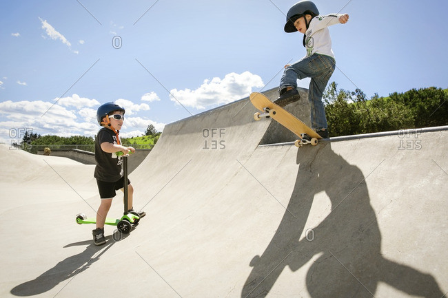 Boy looking at friend performing stunt on skateboard ramp