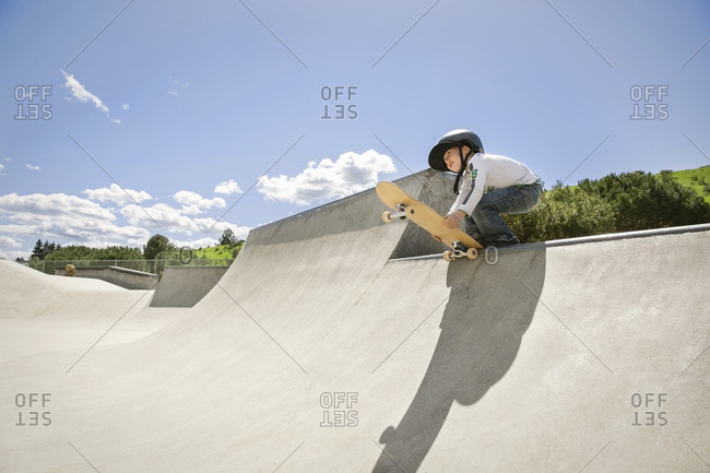 Low angle view of boy holding skateboard on ramp against blue sky