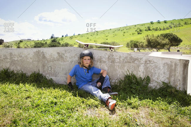 Portrait of confident boy sitting on field at skateboard park