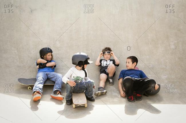 Boys talking while sitting on skateboard ramp