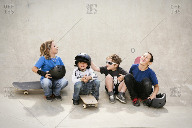 Cheerful boys talking while sitting on skateboard ramp