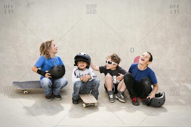 Cheerful boys talking while sitting on skateboard ramp