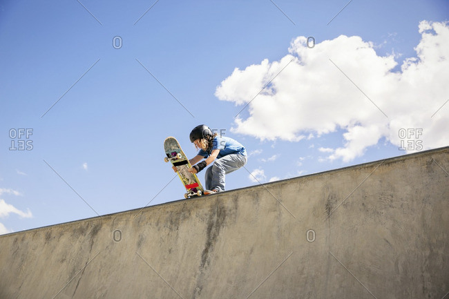 Low angle view of boy placing skateboard on ramp against blue sky