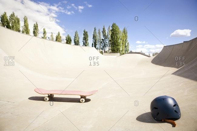 Skateboard and helmet on ramp against blue sky