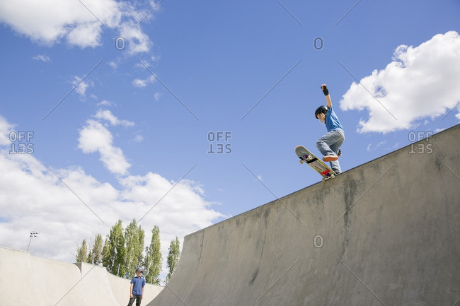 Low angle view of boy skateboarding on ramp against blue sky