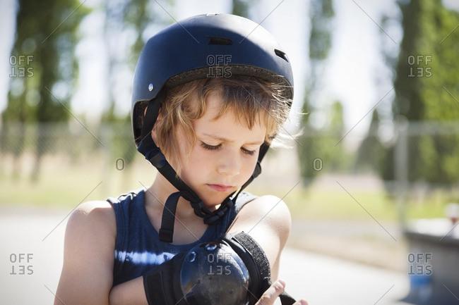Boy adjusting elbow brace at skateboard park