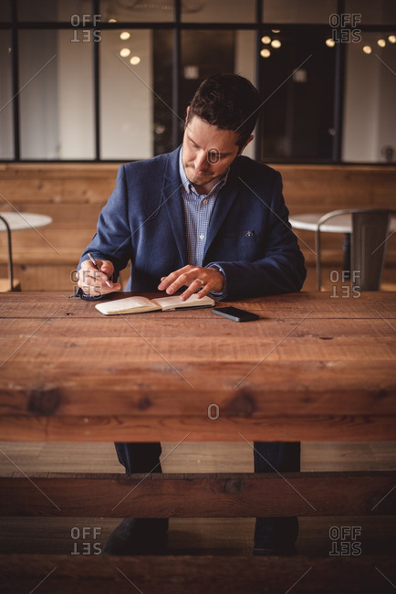 Businessman writing at long wooden table in cafe