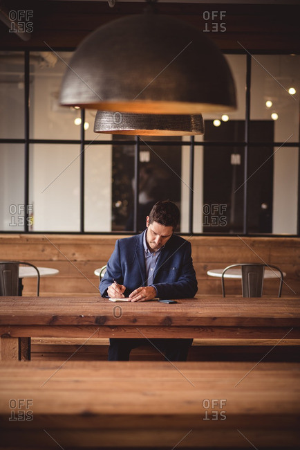 Businessman working at long wooden table in cafe