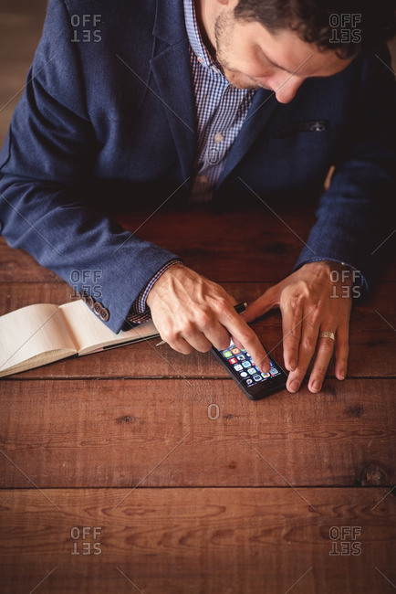 Elevated view of man using smartphone at wooden table