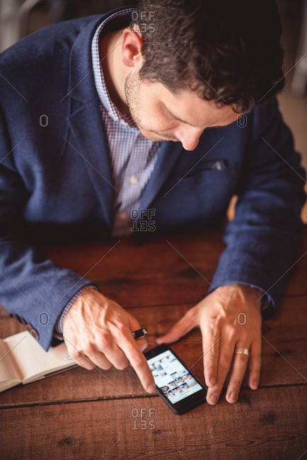 Man looking at photos on smartphone at wooden table