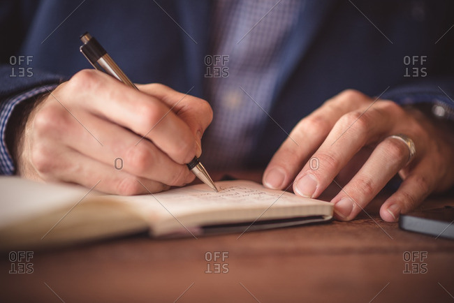 Close-up of man's hands writing in notebook on wooden table