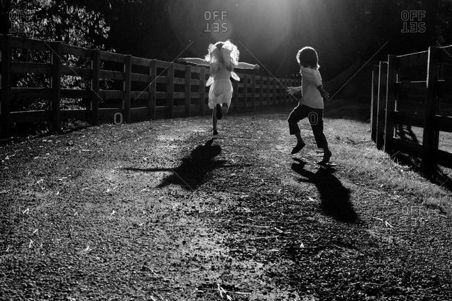Two children running along a gravel road at night