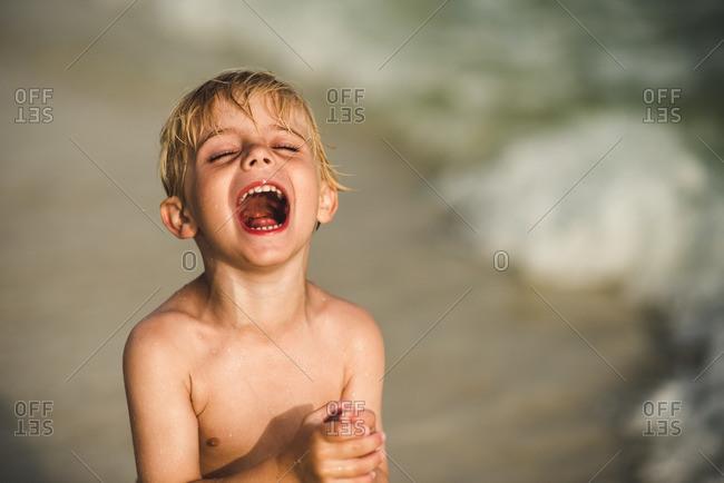 Boy standing on the beach yelling