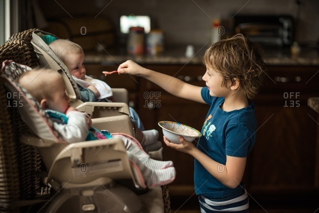 Child feeding twin children in the kitchen