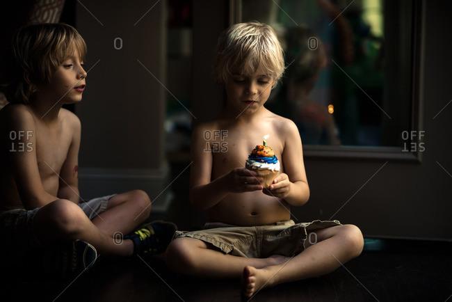Boys celebrating a birthday with a birthday cupcake